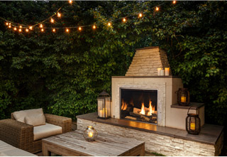 TC36 Outdoor fireplace with Chalet log set and black porcelain firebox panels in outdoor setting